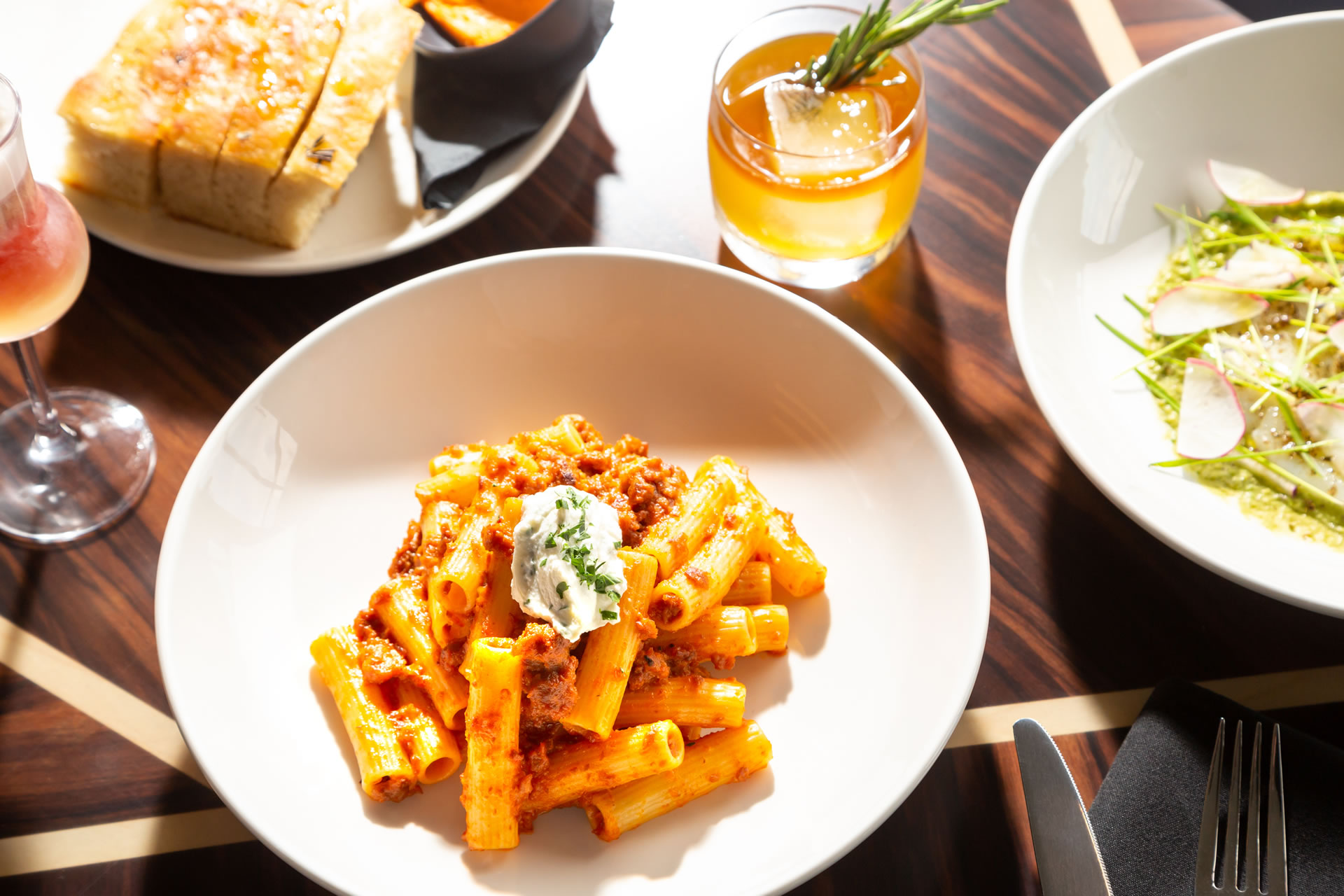 A plate of bolognese among other food on a table at Copper & Salt Northwest Kitchen